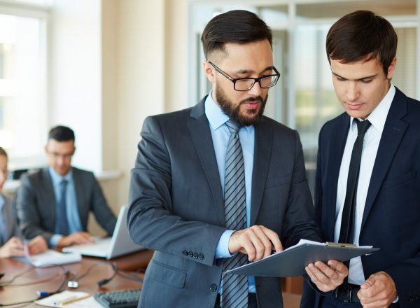 Confident businessman pointing at document while explaining his idea to his partner on background of their colleagues